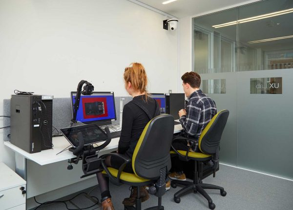 - Image of two people working in NUA's UX Lab. Both people are using a computer whilst being filmed by a tracking camera