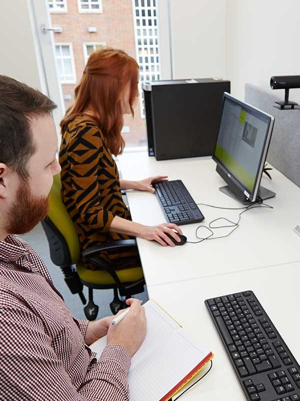 - Image of a woman browsing on a computer in a UX Lab with User Experience Designer watching her