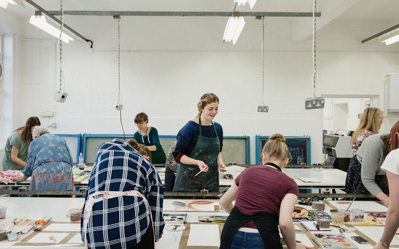 Image of students working in a rpinting studios using paints and hairdryers