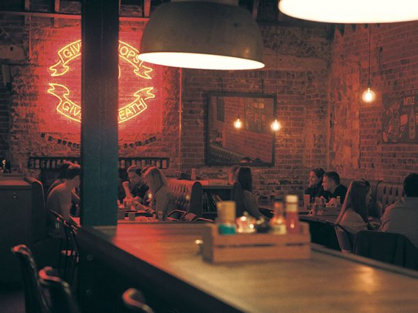 Brewdog Bar - Image of the interior of a bar featuring a neon bar sign and people sitting at desks