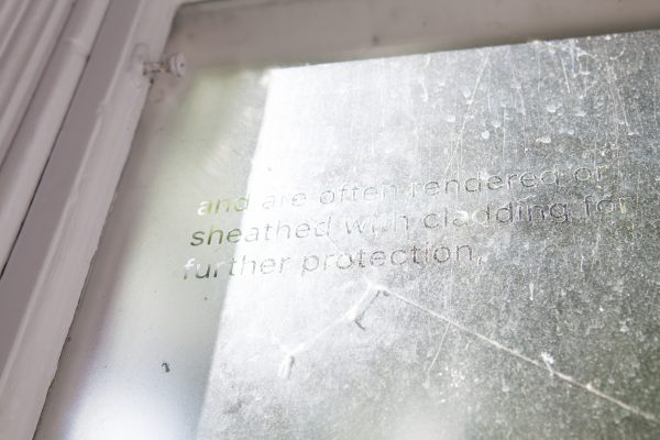 - Photograph from BA Degree Show 2017 of a frosted window with clear text