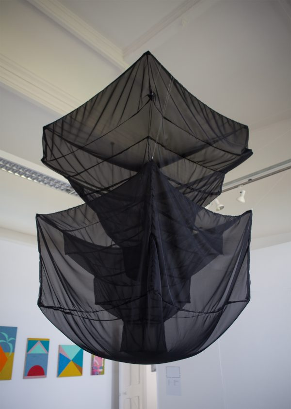 - Photograph of large geometric black mesh sculpture hanging from ceiling in BA Degree Show 2017