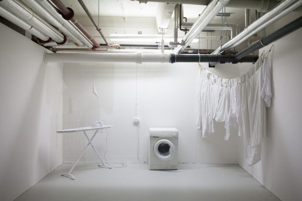 - Installation from BA Degree Show 2017 of a white washing machine, ironing board and hanging clothes in a white space