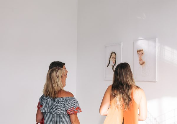 - Photograph of three people looking at painted portraits in 2017 BA Degree Show