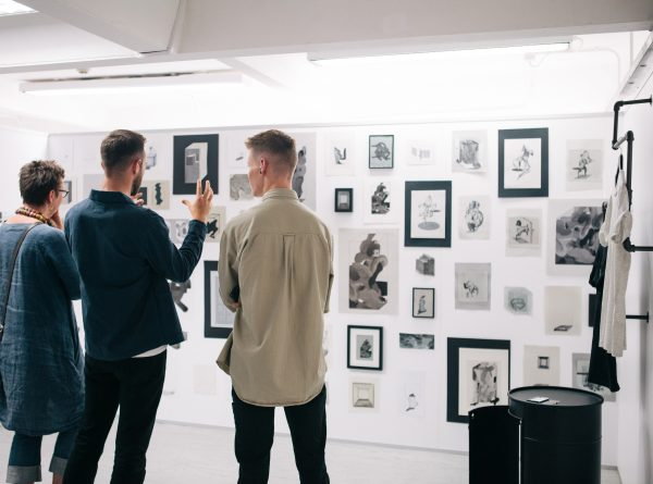 - Three people looking at a wall full of framed drawings in the 2017 BA Degree Show