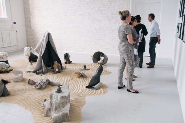 - Sculptures in the middle of the room on sand with people looking at work on the walls