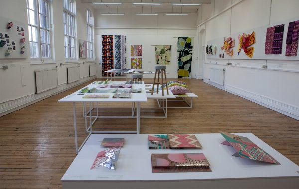 - Large room with wooden floor displaying textile design work on tables and walls in 2017 BA Degree Show