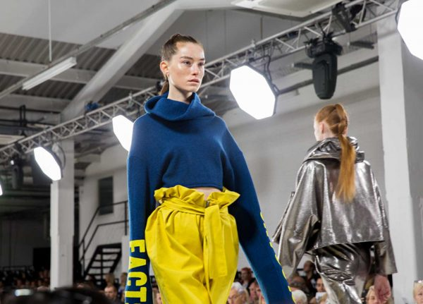 Meg Tovery - Image of a model wearing a blue jumper and yellow trousers on the catwalk at Graduate Fashion Week