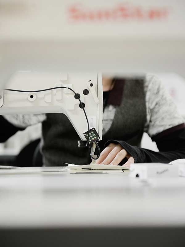 Image of a student using a Fashion sewing machine in the NUA fashion studios