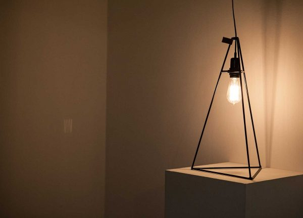 - Image of a metal framed lamp in a dark studio space, the lamp is lit and shines a yellow light into the space