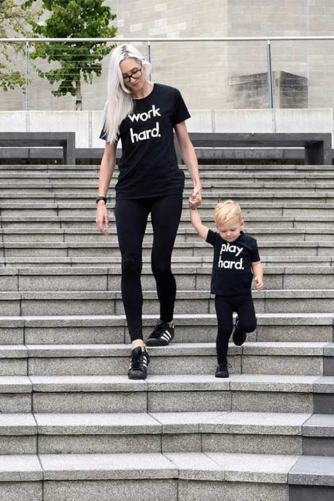 Image of a woman and a child walking down concrete steps wearing black t-shirts with the words Work Hard on