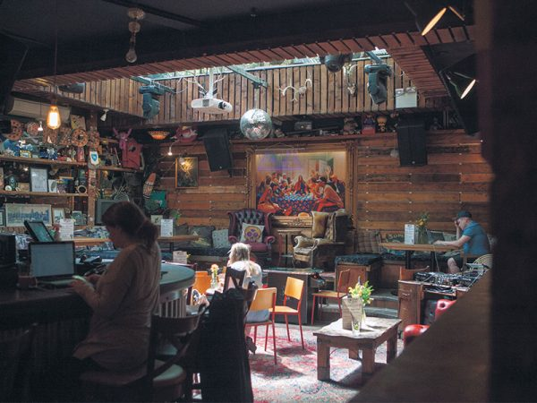 Gonzos Tea Room - Image of people sat in a bar which featuring wooden walls and large paintings, plants and contemporary seating
