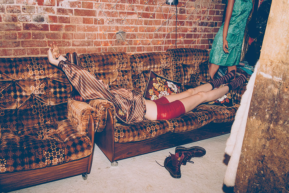 Girl lying on a vintage brown sofa in brown top and red hot pants next to pair of boots by Kerry Curl.