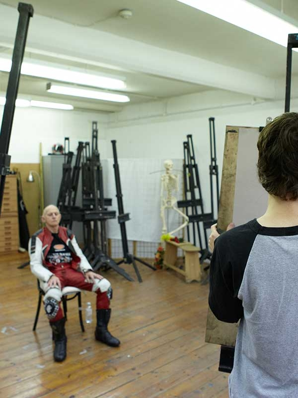 Image of an NUA student drawing on an easel in the NUA life drawing studio. Student draw a male model dressed as a biker