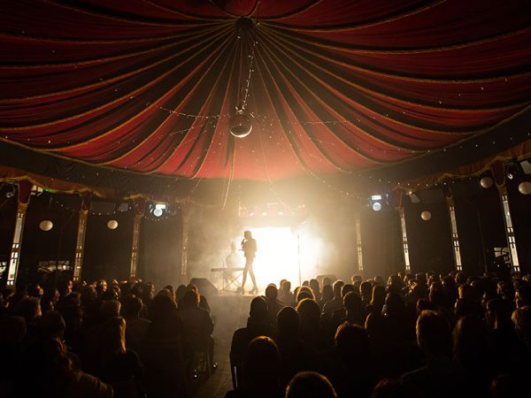 Norfolk and Norwich Festival - Image of a performer on a stage in front of a back lit audience and under a red canopy