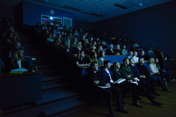 - Photograph of NUA's darkened lecture theatre full of guests at an open day