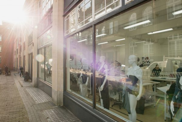 - Photograph of NUA's Gunton's Building window from the outside looking in, with fashion mannequins on the inside