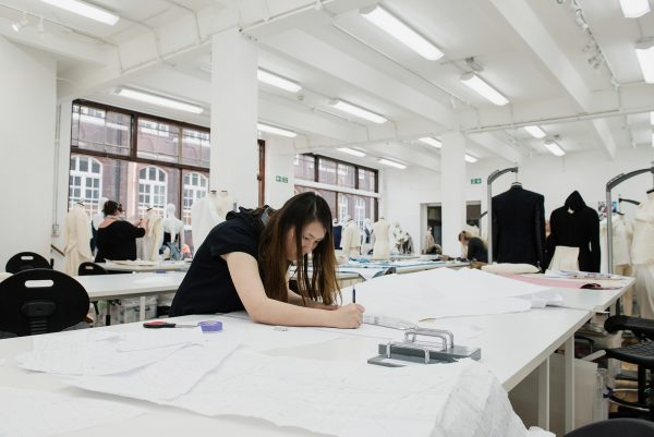 - Photograph of three students at work in NUA's fashion studios