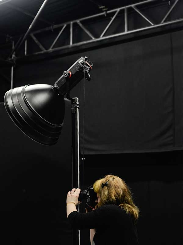 Image of a student taking a picture in the NUA Photography studio