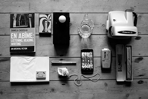 John Boursnell - Work by Norwich University of the Arts Research Student John Bournsell showing various objects on a table including matches, shell, phone, glass, ball, camera and book