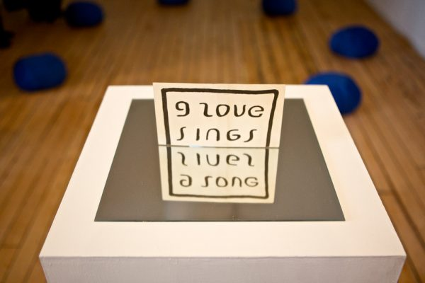 Nicola Simpson - Work by Nicola Simpson, Fine Art Research Student at Norwich University of the Arts stating 'I Love Sings' on plinth