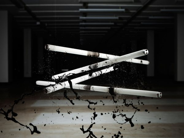 Simon Bell - Image of four tubes of strip lighting hanging in the air with black paint being dropped on them from above