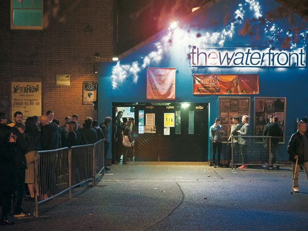 The Waterfront Music Venue - Image of the exterior of a blue building featuring a lighted sign with the title The Waterfront