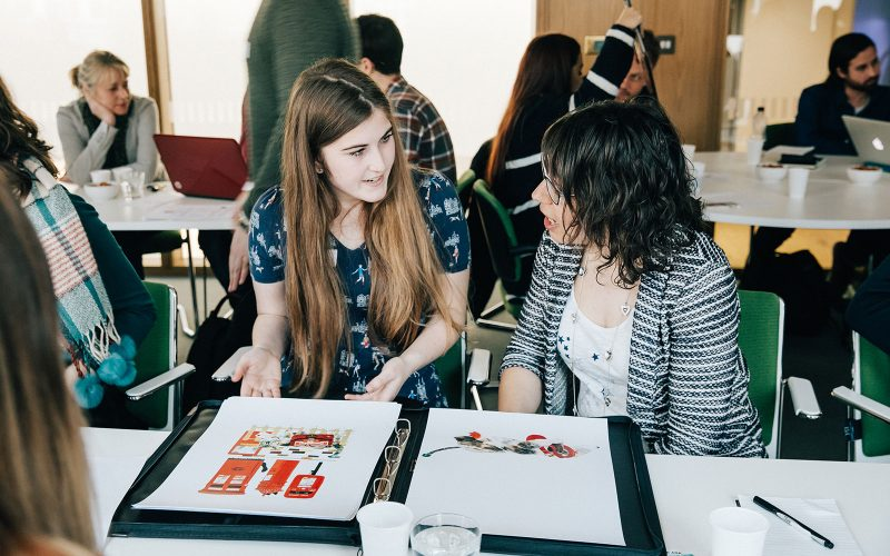 Student shows colourful portfolio book to industry guest at Big Book Crit, Norwich University of the Arts