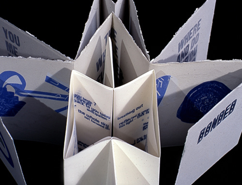 Bookwork - Aerial image of a white concertina book printed with blue text, partially folded out and standing upright