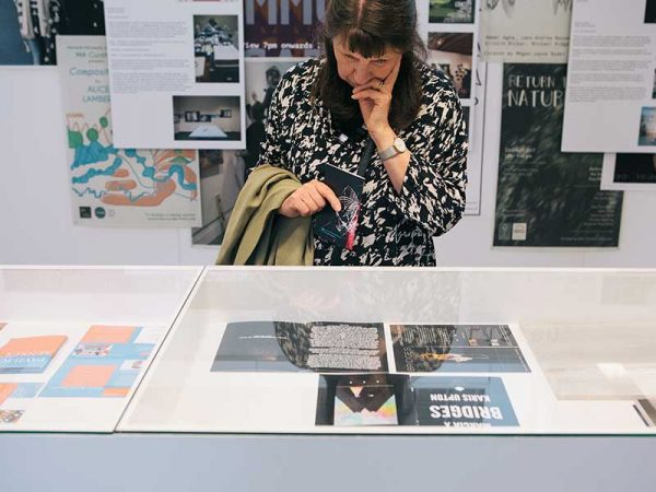 MA Curation - Image of a female visitor looking in a vintrine of publications at the MA Degree Show 2017