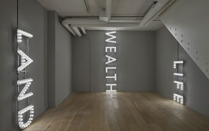 LED word display saying Wealth, Land, Life, by Nathan Coley.