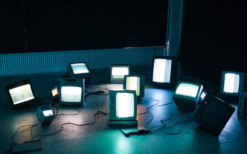 Image of several vintage televisions sets arranged on a floor in a drak studio space, the light from the screen creates shadows on the floor, created by MA Moving Image and Sound student Neil James Earl