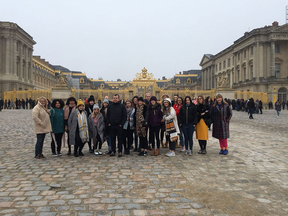 Textile Design students stand outside of the Paris Versailles Paris gates