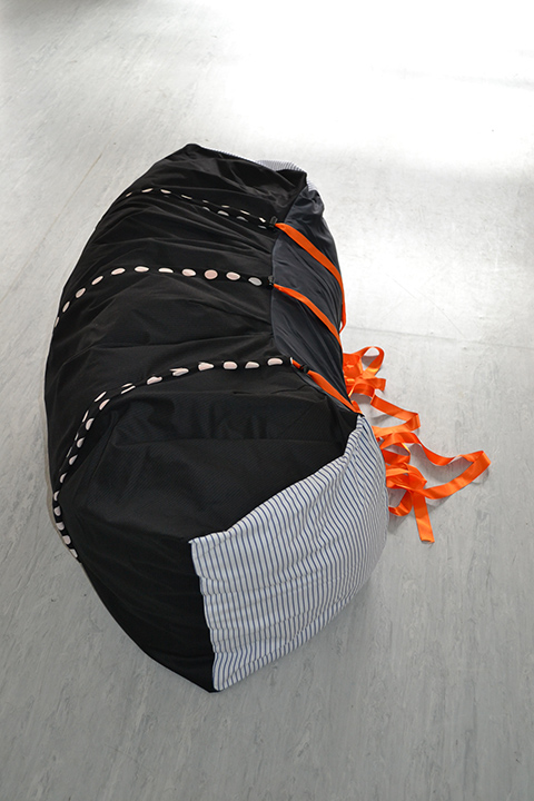 Let's Get Comfortable - Solid fabric rectangular shape on the floor made of mostly black fabric, with white stripes at one end and orange ties along one long side