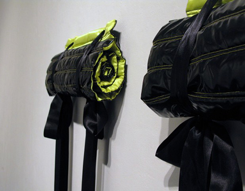 Untitled - Photograph of rolled up black and lime green fabric shapes attached to a white wall