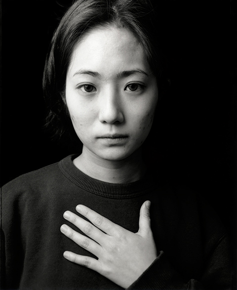 Untitled - Black and white portrait of a young woman looking at the camera with her left hand on her chest