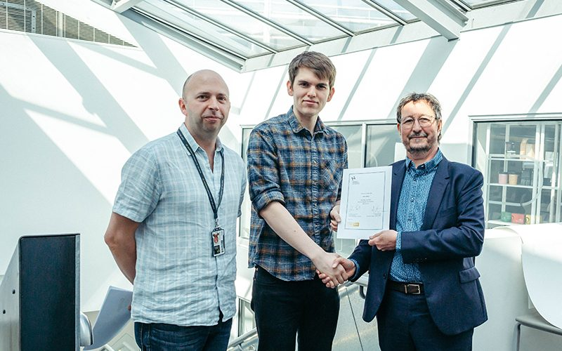 Photograph of Nic Hughes Travel Prize winner John Miller, receiving his certificate from Professor John Last and Graphics course leader Martin Schooley