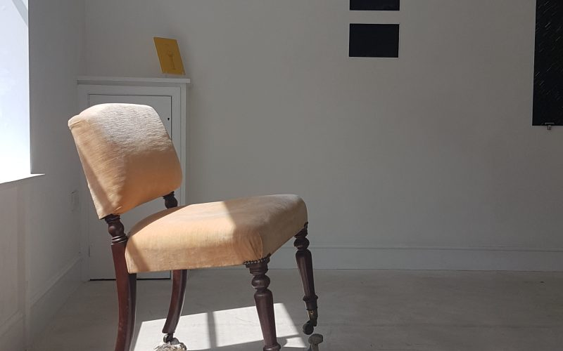 Chair balanced on stones in light coming through a window, by Jade Jamean Lees and curated by Kate Knowlden