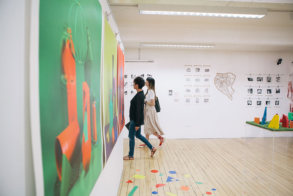 Visitors look at colourful illustration work in the Norwich University of the Arts Degree Shows