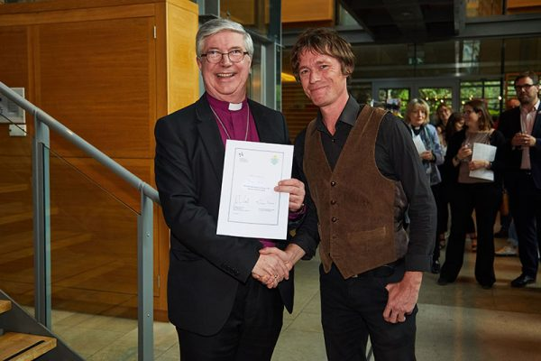 The Bishop of Norwich and Julian Hand, MA Moving Image and Sound - Bishop of Norwich presents Norwich University of the Arts student Julian Hand with the winning certificate at the Bishop's Art Prize 2018