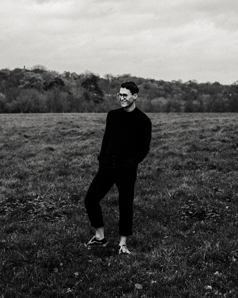 BA Film and Moving Image Production student Dan Franklin stands on a field in a black and white photo. Image by Sam Shepherd, BA Photography