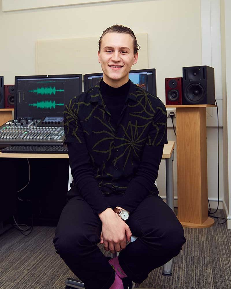 Dan Franklin, a BA Film and Moving Image Production student sits in the film studio control room at NUA