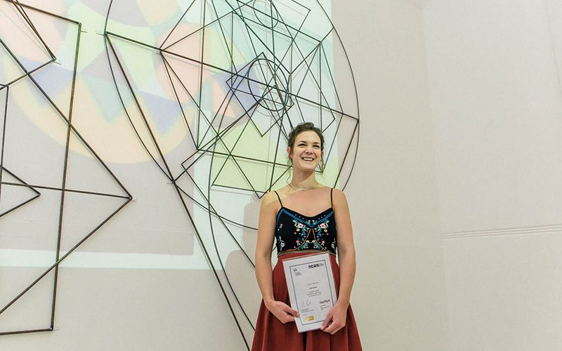 NCAS Prize 2018 winner Beth Bartlett with certificate standing in front of projected work covered in metal frame