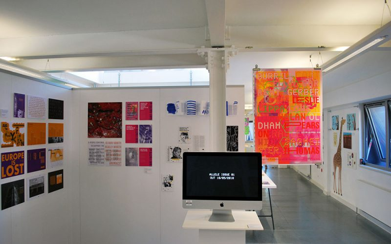 Mac screen showing graphics Degree Show work in front of other Degree Show work at Norwich University of the Arts