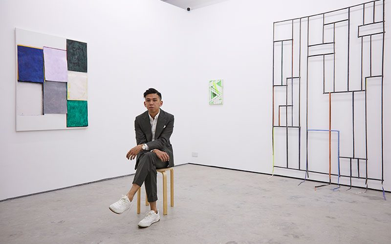 Gabriel Loy, Fine Art graduate at Norwich University of the Arts sat in his gallery 1961 in Singapore