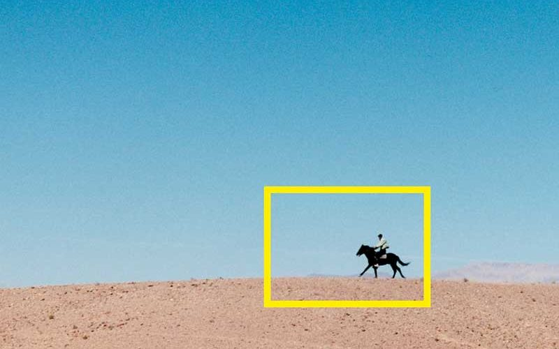 Photo of person riding a horse on sand, surrounded by imposed yellow box
