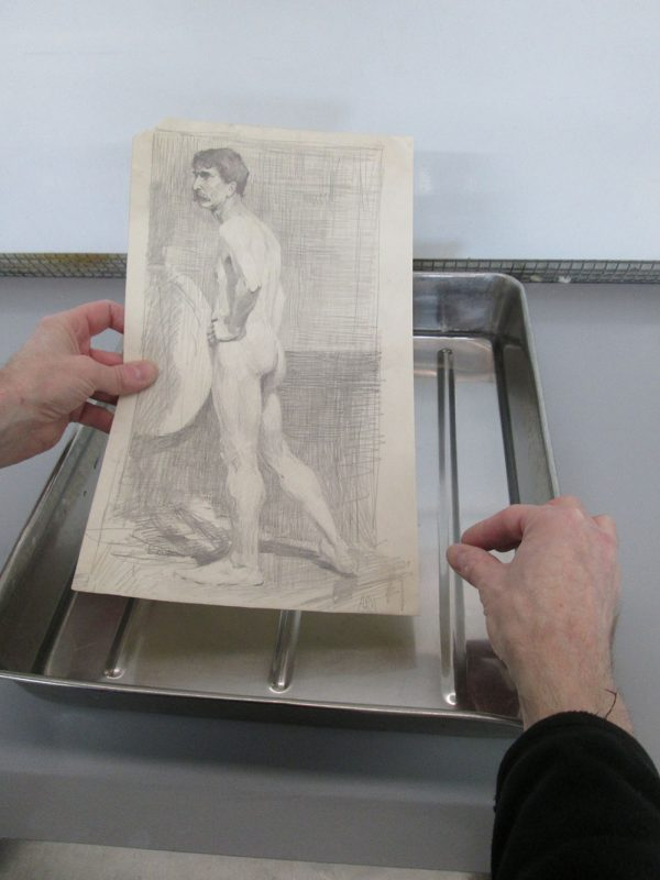- Person holding painting of Munnings drawings restoration process - a drawing of a naked man