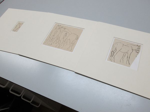 - Mounts of Munnings Drawing laying on table during restoration process