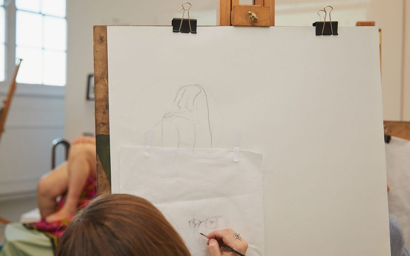 Student draws life model in the Munnings Drawing Studio at Norwich University of the Arts