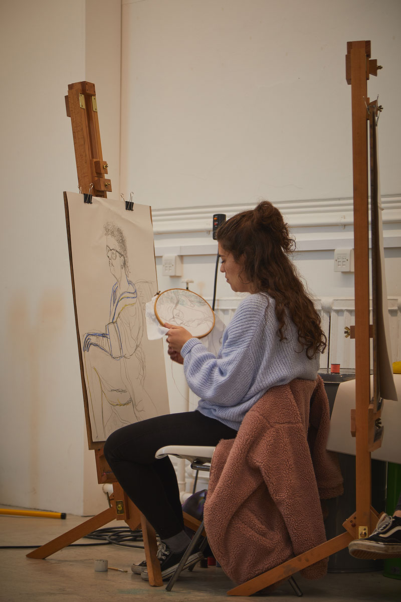 Student works sewing canvas in Munnings Drawing Studio at Norwich University of the Arts